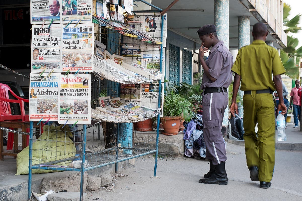 A security guard reads the newspapers' headlines at a newsstand in Mwanza. (AFP)