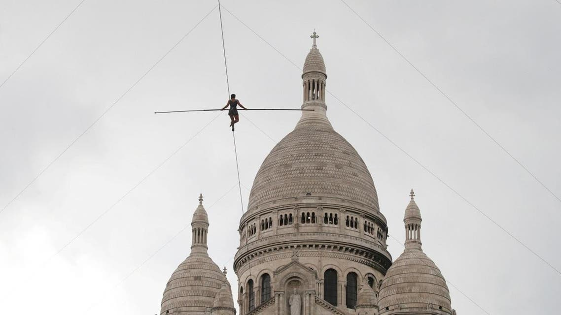 Tightrope walker Tatian-Mosio Bongonga advances on a tightrope as she scales the Monmartre hill towards the Sacre Coeur Basilica in Paris. (Reuters)
