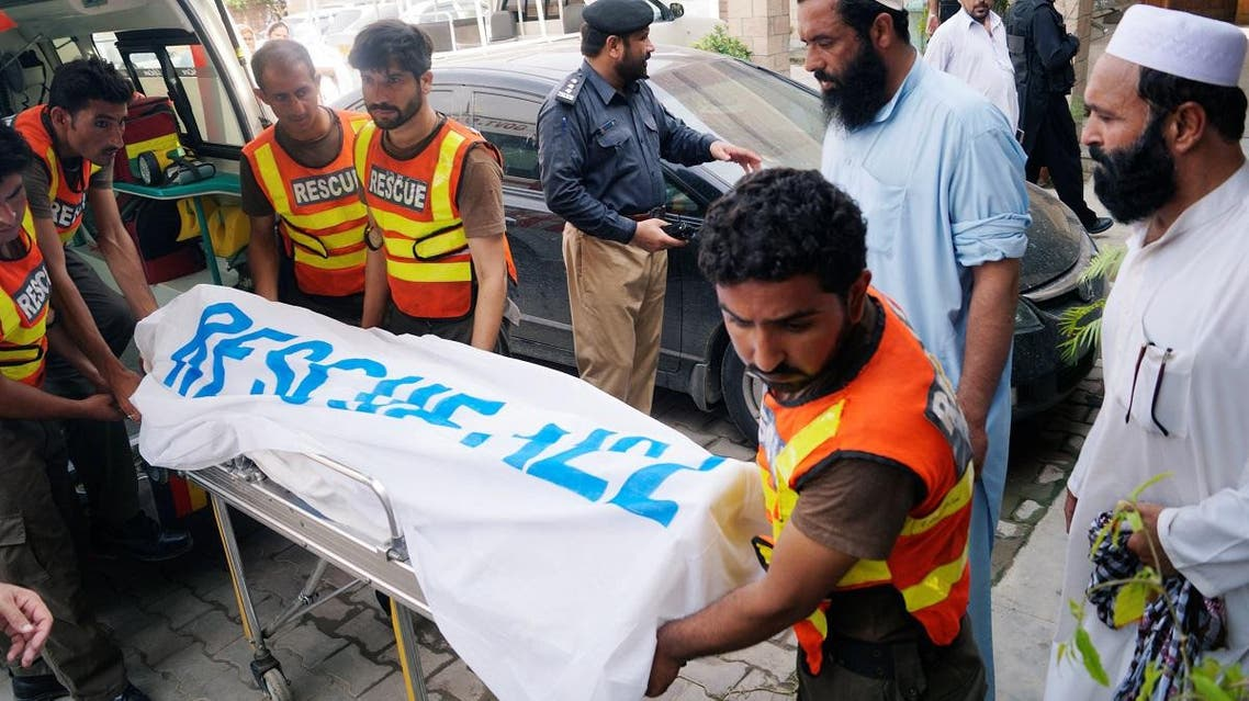 Rescue workers move the body of Ikramullah Gandapur, a candidate of the Pakistan Tehreek-e-Insaf (PTI), or Pakistan Justice Movement, who was killed in a suicide attack, outside hospital morgue in Dera Ismail Khan. (Reuters)