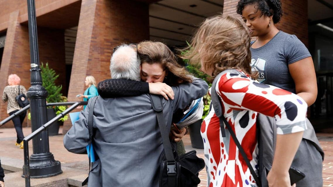 Former New York Daily News newspaper editorial staff members embrace outside the newspaper's offices in New York City after layoffs in New York. (Reuters)