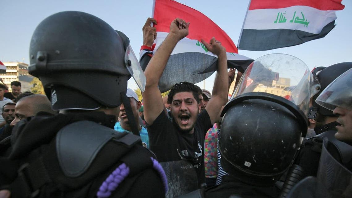 Iraqi protesters shout slogans and wave national flags as they facing security forces during clashes at a demonstration against unemployment and a lack of basic services in the capital Baghdad's Tahrir Square. (Reuters)