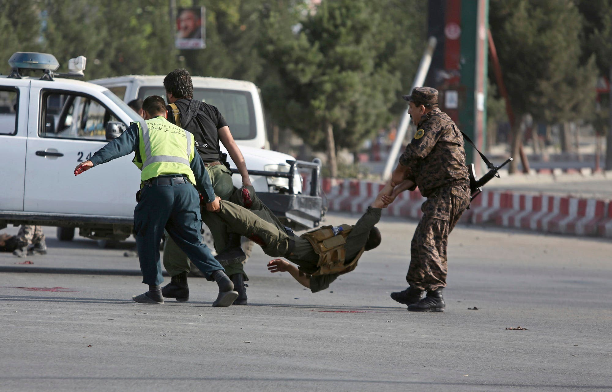 Afghan security personnel carry an injured officer after an attack near the Kabul Airport, in Kabul, Afghanistan, Sunday, July 22, 2018. (AP)