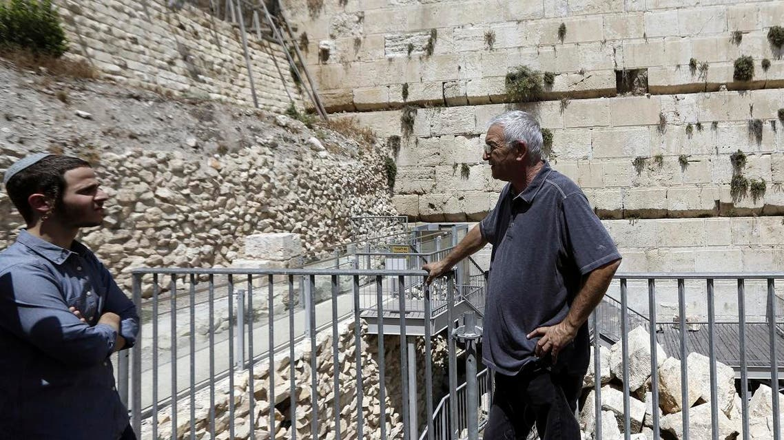People stand near the part f the Western Wall where one of the stones dislodged and crashed into the prayer area in Jerusalem. (AP)