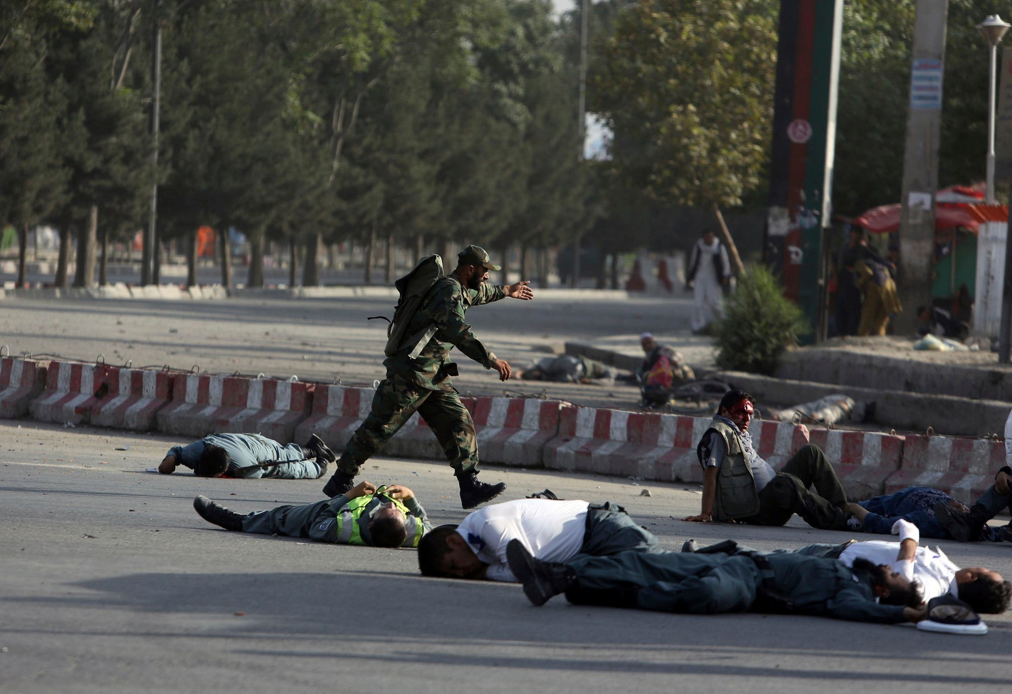 Afghan security personnel and traffic police lie on the ground after a suicide attack near the Kabul Airport, in Kabul, Afghanistan, Sunday, July 22, 2018. (AP)