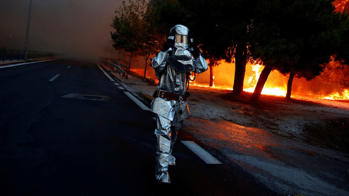 A firefighter wears a flame resistant uniform as wildfire burns in the town of Rafina, near Athens, Greece, July 23, 2018. REUTERS/Costas Baltas