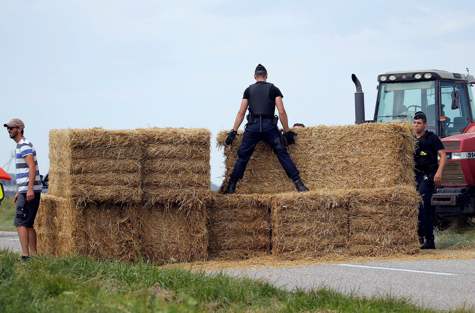 Police officers remove hay bales off the road after the protest on July 24, 2018. (Reuters)