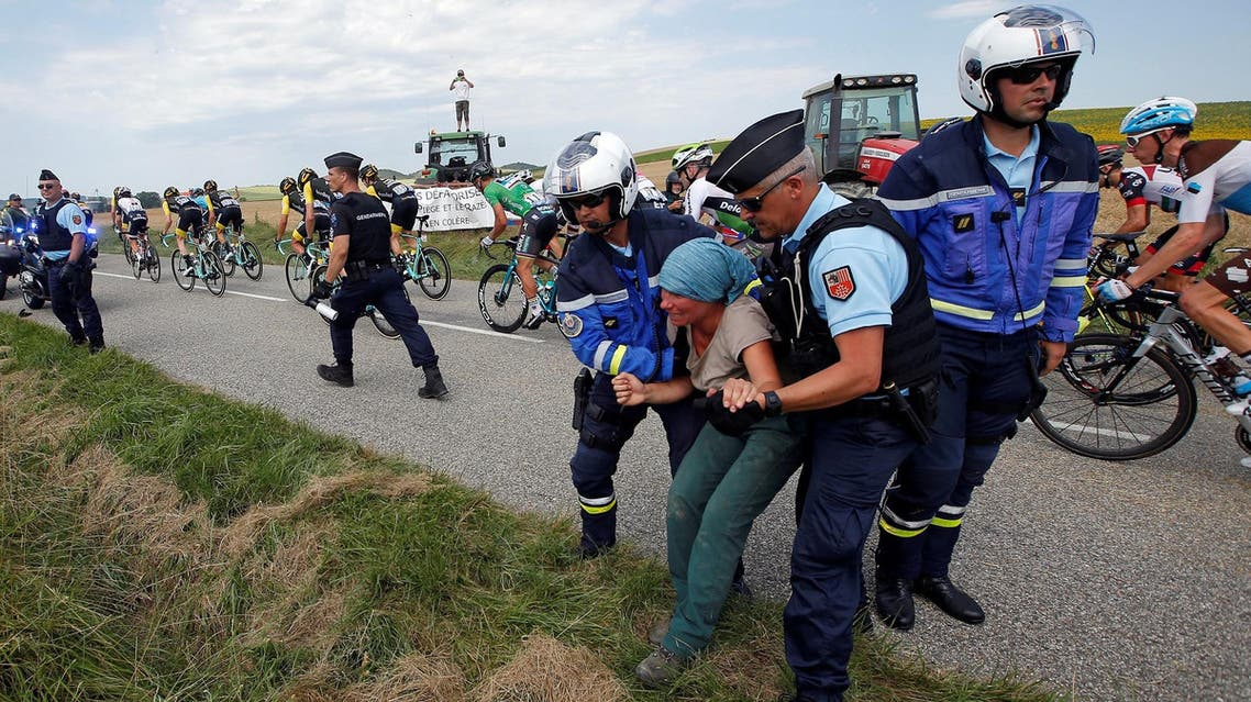 Police officers carry a protester off the road as the peloton passes. (Reuters)