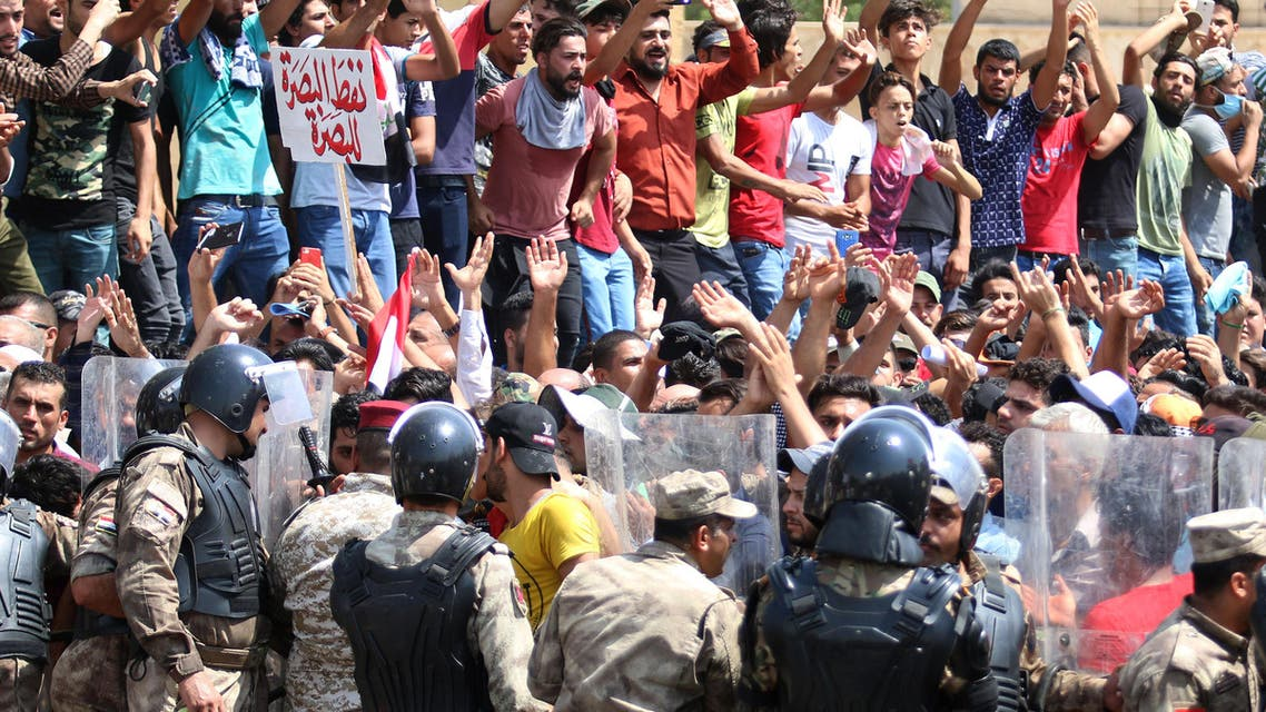 """Iraqi riot police lined up as protesters chant slogans and hold up signs during a demonstration in Basra on July 15, 2018. The arabic sign in red at top left reads:""""Basra oil for Basra"""". Dozens of demonstrators were wounded in southern Iraq today in clashes with police as protests over unemployment and a lack of basic services entered a second week, officials said."""