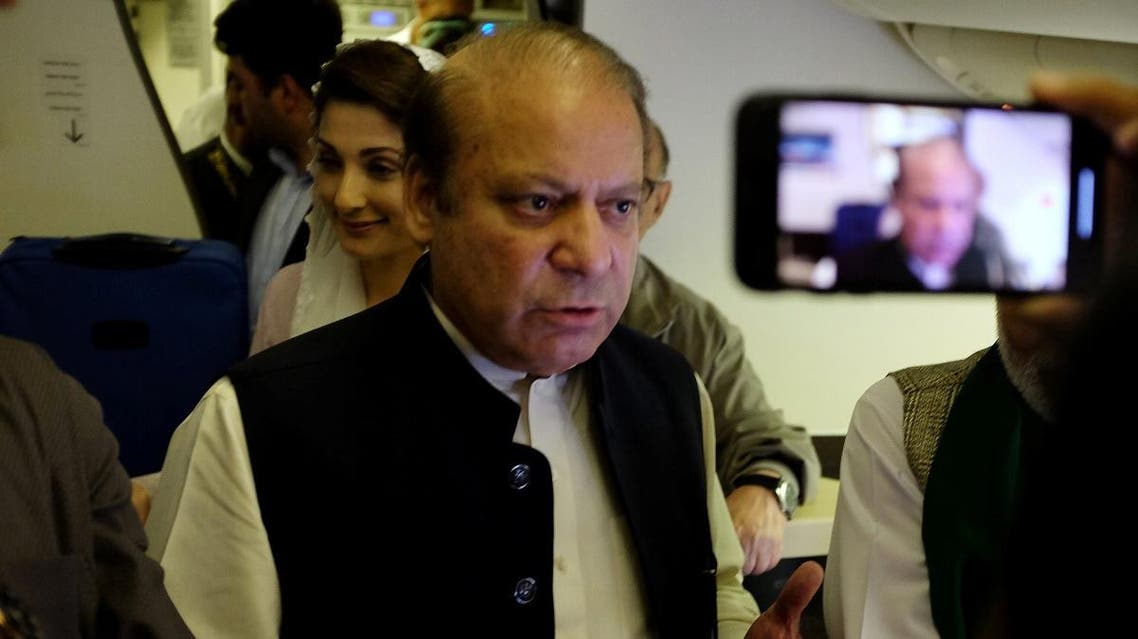 Ousted Pakistani Prime Minister Nawaz Sharif gestures as he boards a Lahore-bound flight due for departure, at Abu Dhabi International Airport. (Reuters)