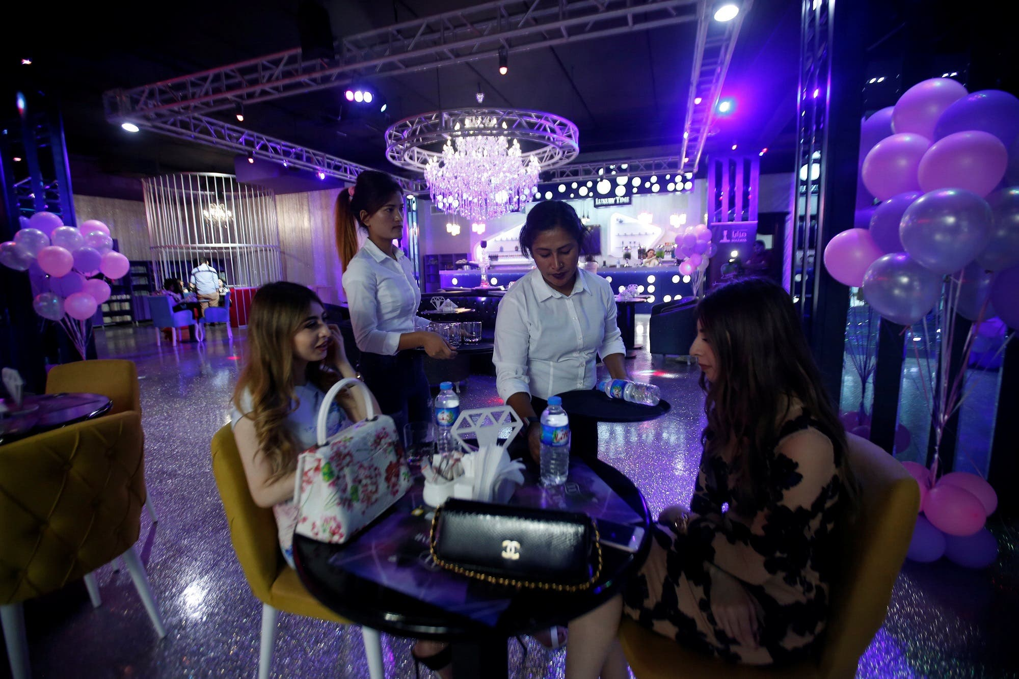 Waitresses serve an order at Luxury Time in Erbil on July 17, 2018. (Reuters)