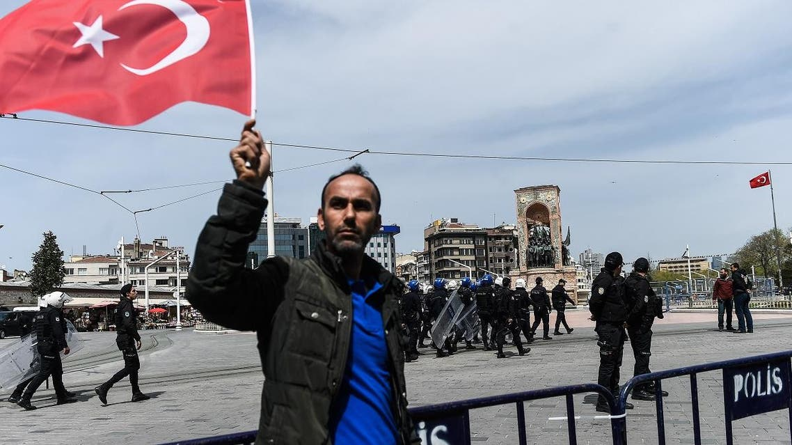 A man waves Turkish flag as (background) Turkish security officers. (AFP)