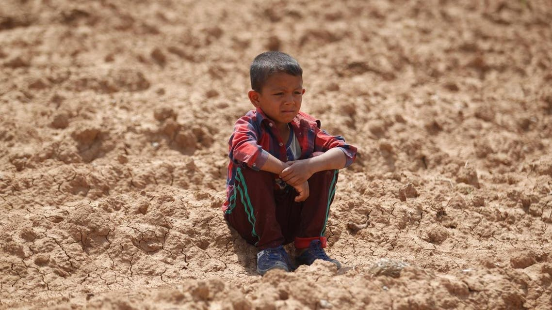 An Iraqi boy sits in an agricultural field north of Mosul. (Reuters)