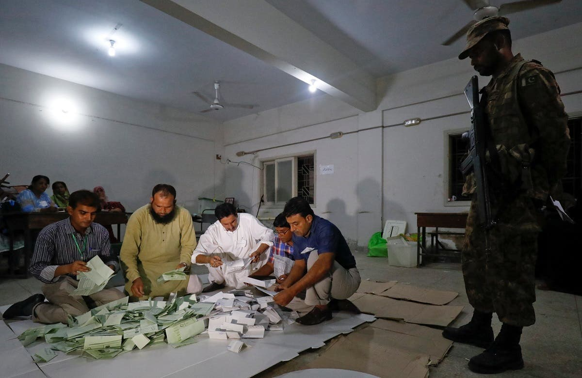 Election officials count votes after polling stations closed during the general election in Karachi. (Reuters)