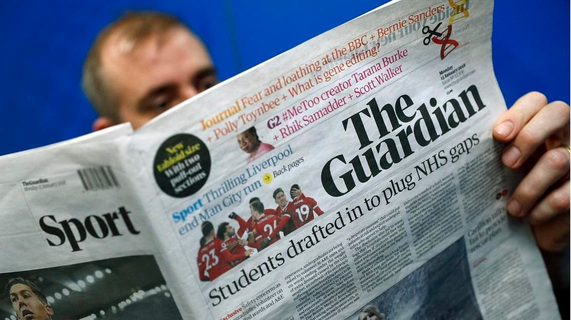 A man poses holding up a copy of the new look tabloid Guardian national newspaper. (AFP)