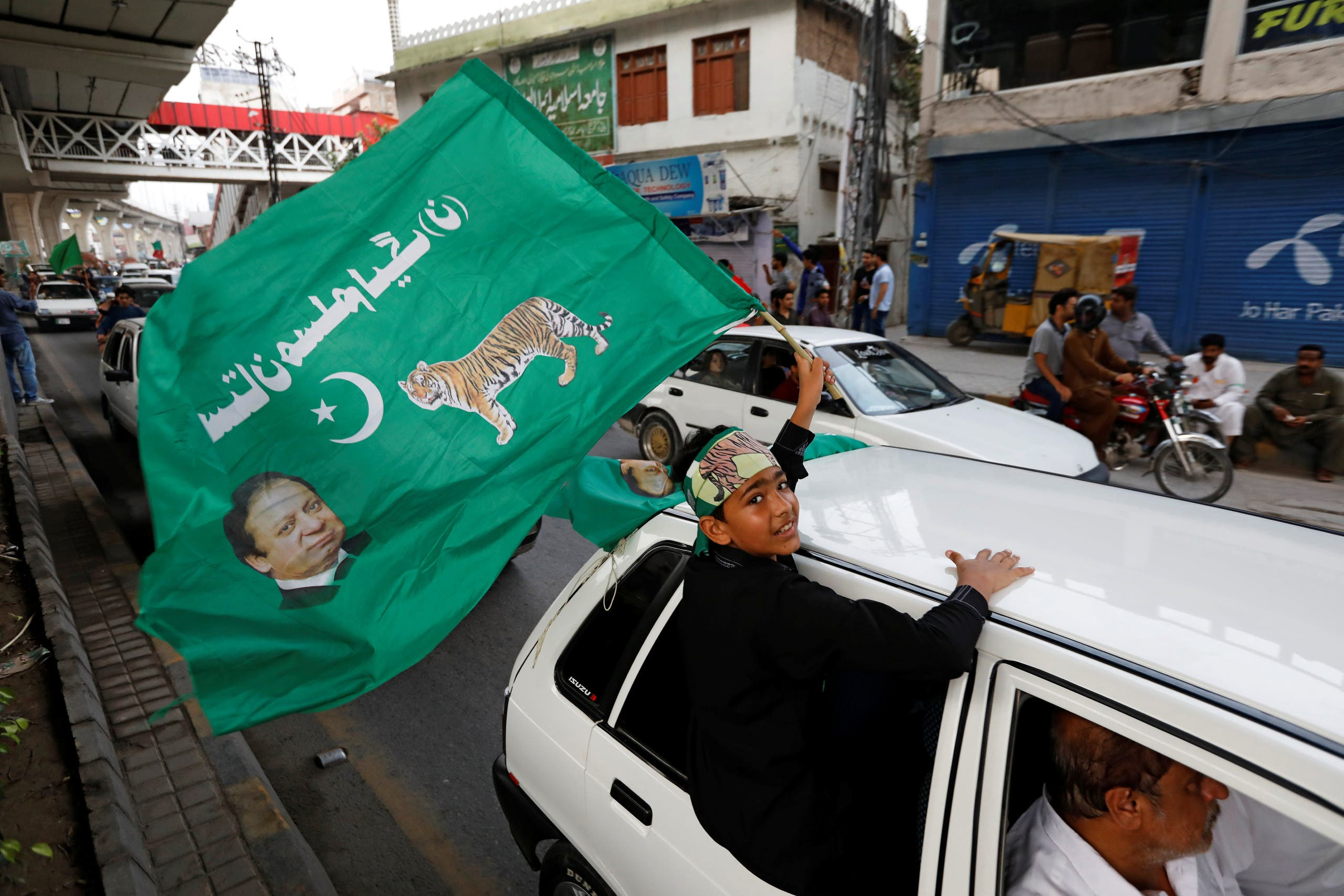 A supporter of Pakistan Muslim League-Nawaz (PML-N), waves a party flag during the general election in Rawalpindi on July 25, 2018. (Reuters)