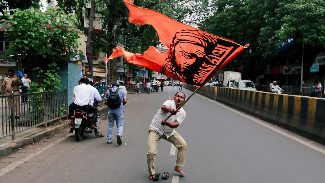 A man waves a flag as he blocks a road during a protest in Mumbai on July 25, 2018. (Reuters)