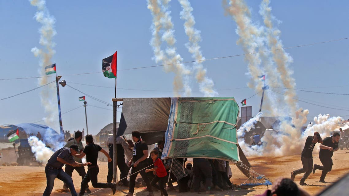 Palestinians run for cover from tear gas near the border between Israel and the Gaza Strip on May 14, 2018. (AFP)