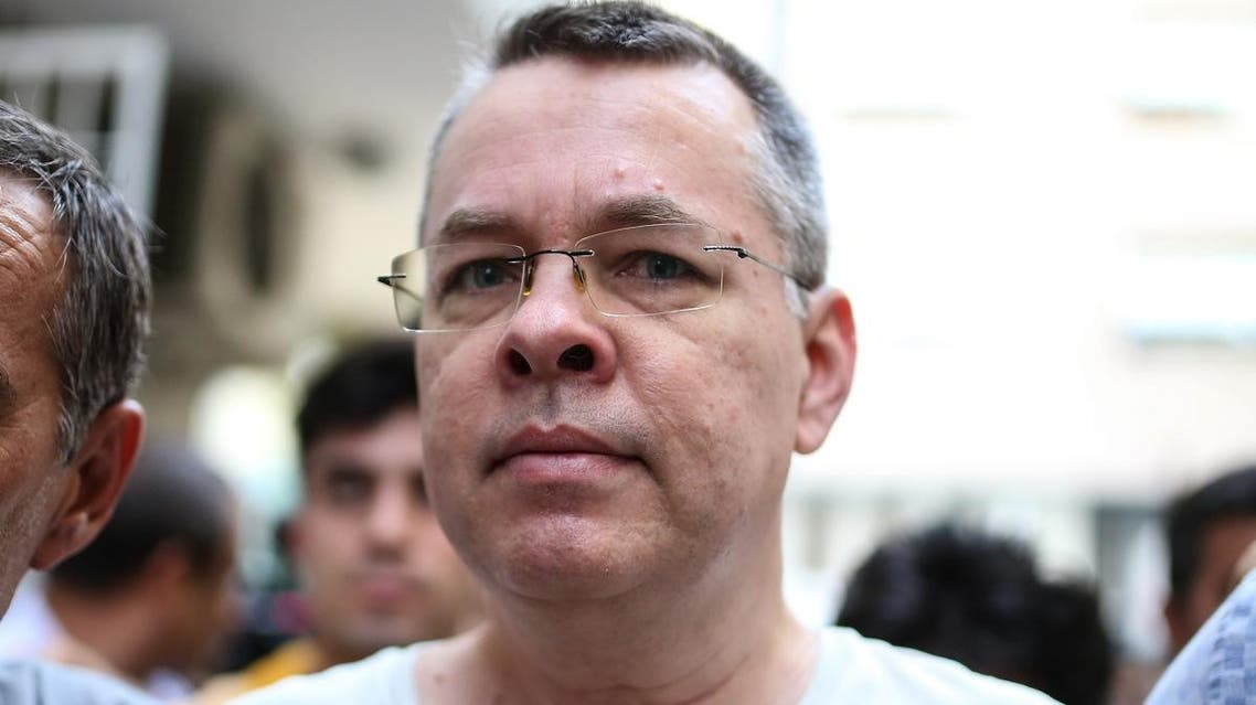 In this file photo taken on July 25, 2018 US pastor Andrew Craig Brunson is escorted by Turkish plainclothes police officers to his house on in Izmir. (AFP)