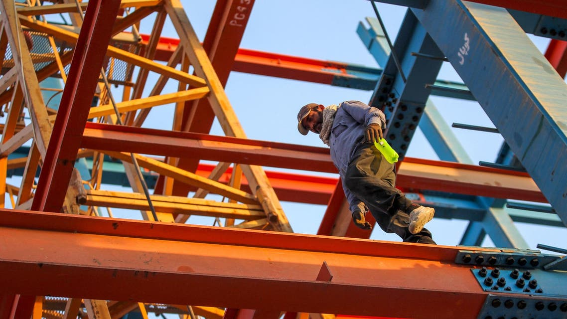 An Iranian construction worker walks on a steel I-beam at a site in Baghdad on June 28, 2018. (File photo: AFP)