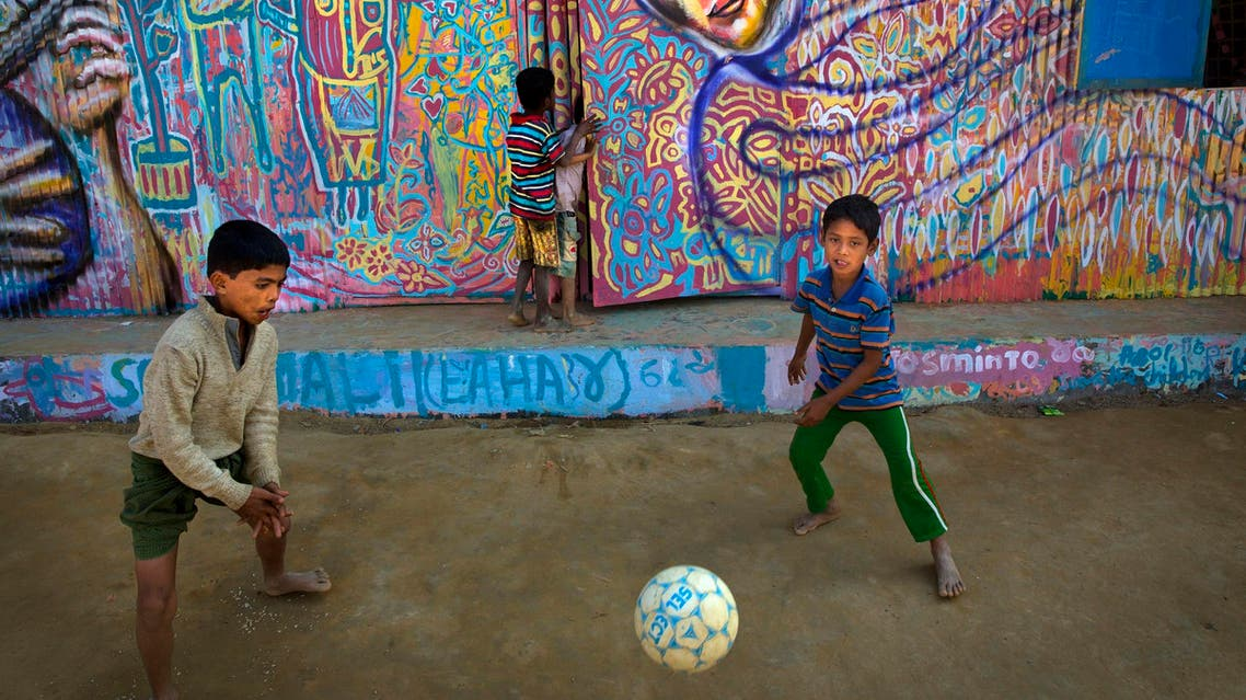 Rohingya refugee children outside makeshift school in Cox's bazar, Bangladesh, with mural created by Artolution on Jan. 21, 2018 (AP)