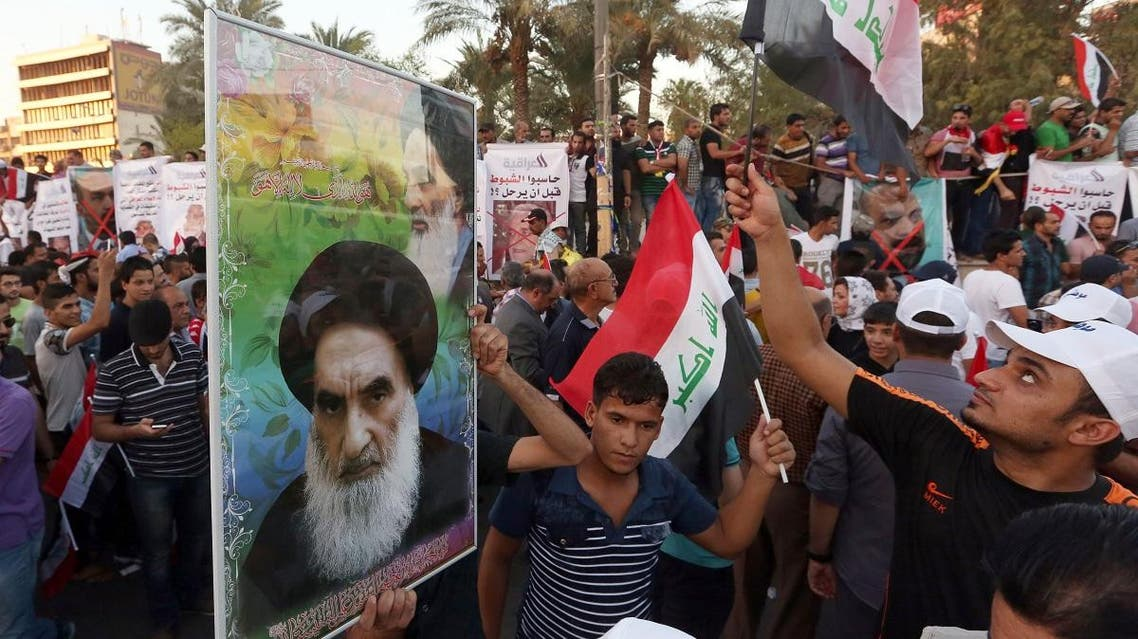 Protesters chant in support the Shiite spiritual leader Grand Ayatollah Ali al-Sistani, in the poster at left, during a demonstration. (AP)