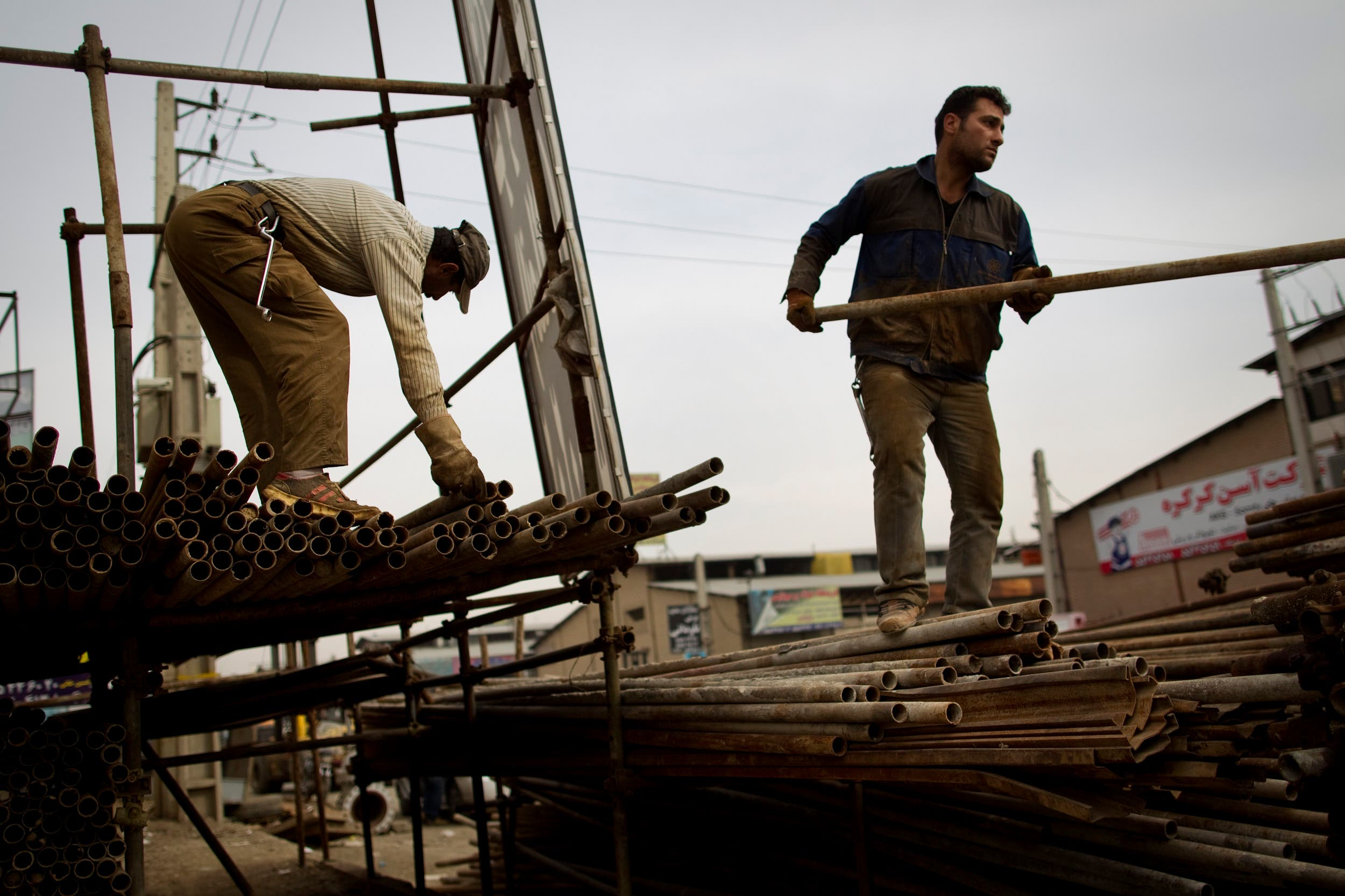 Iranian workers load scaffolding onto a pick-up truck at an iron market in Tehran on February 25, 2012. (File photo: AFP)