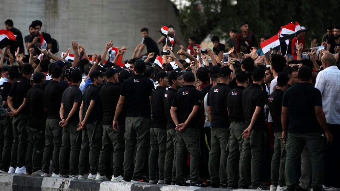Security forces stand guard as Iraqis wave national flags and hold up signs during a demonstration against unemployment in the capital Baghdad's Tahrir Square on July 27, 2018. (AFP)