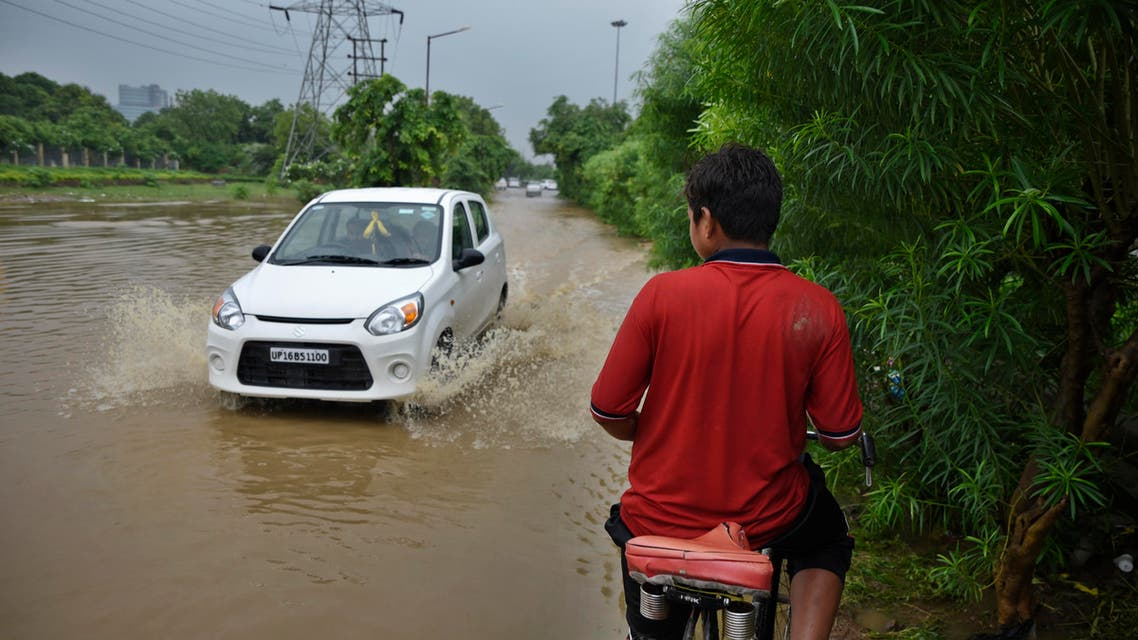 An Indian youth on a bicycle waits for a car to pass as he negotiates his way through a flooded road following monsoon rains in Greater Noida, India, Friday, July 27, 2018. (AP)