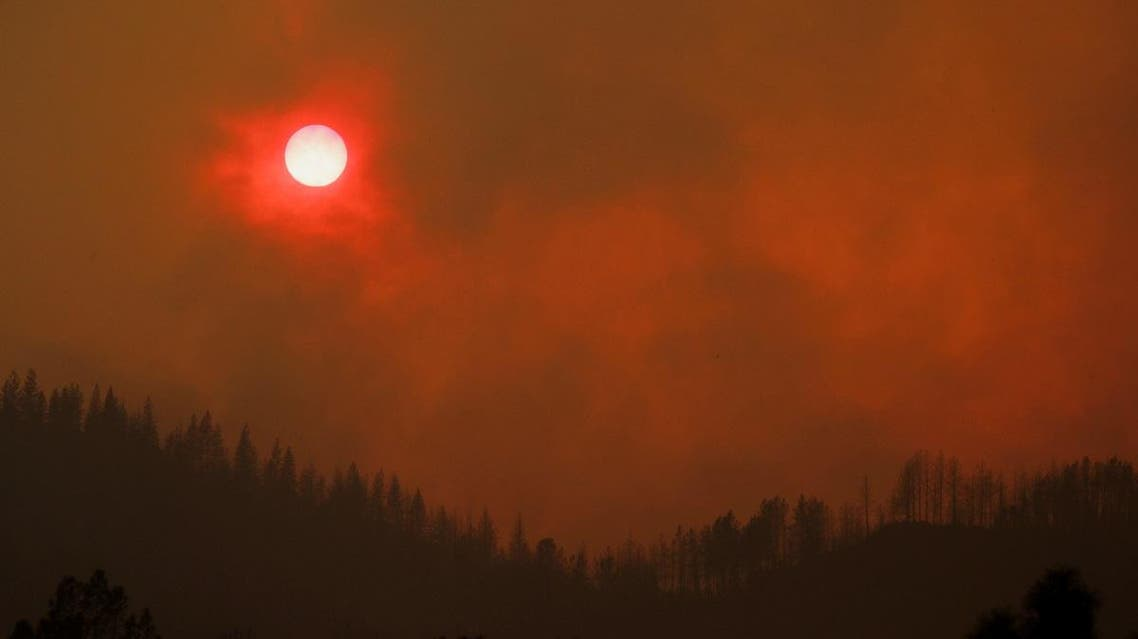 The setting sun is turned red by the smoke from the Carr Fire burning in the hills west of Redding, California, US, July 27, 2018. (Reuters)