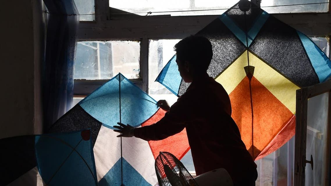 Shohaib, a son of kite vendor Halim Muhammadi, sorts out kites in their home in Kabul. (AFP)