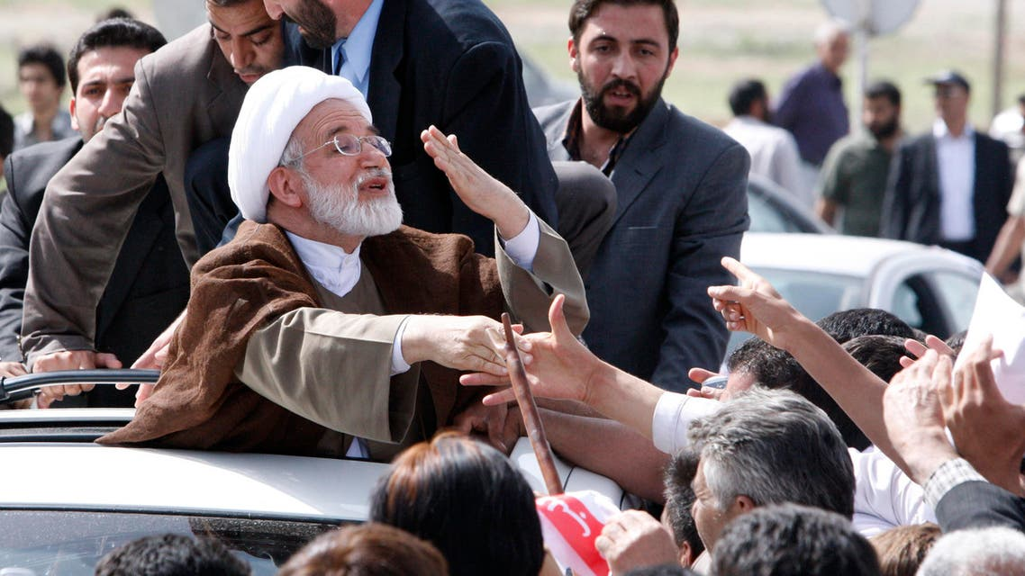 Reformist Iranian presidential candidate, Mahdi Karroubi, sends a flying kiss to his well wishers, as he arrives at his home town of Aligoudarz, during his campaign tour in 2009. (AP)