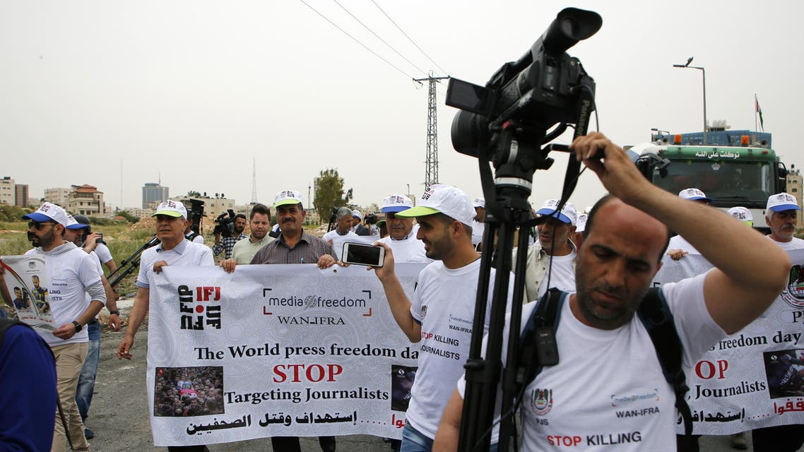 Palestinian journalists hold a banner with photos of two journalists recently killed in Gaza during a protest near Ramallah, on May 6, 2018. (File photo: AFP)
