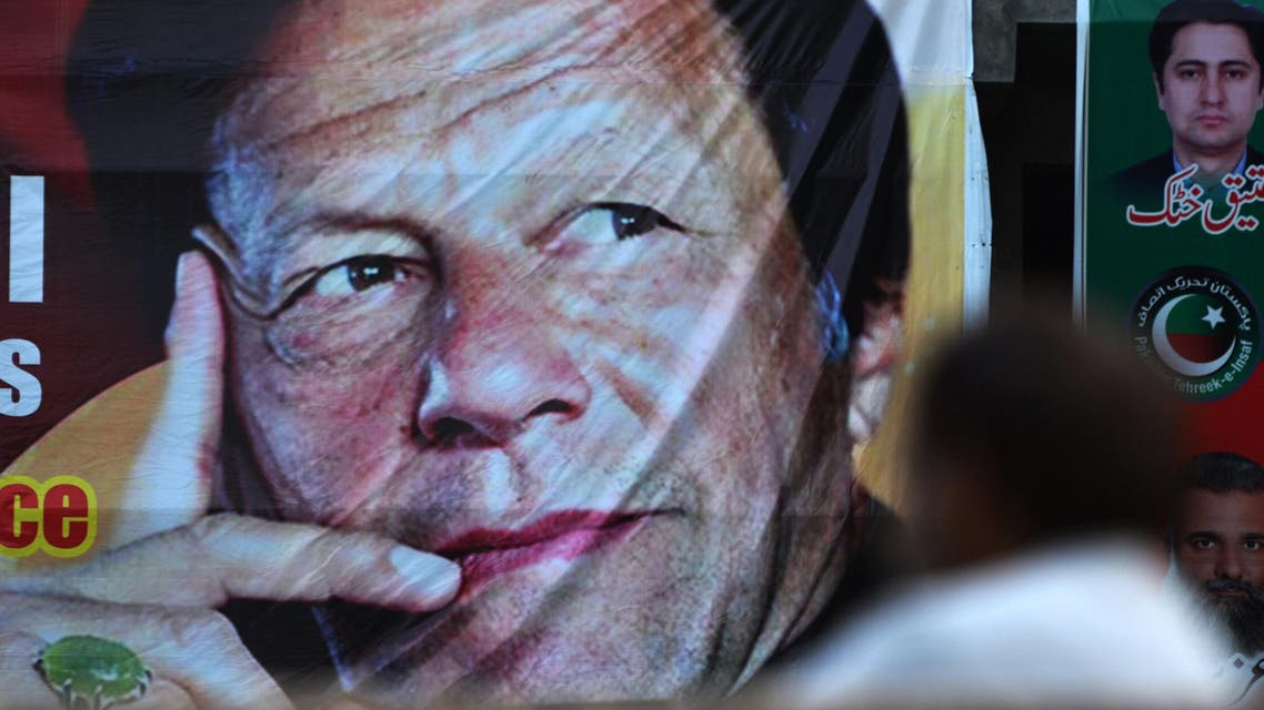 A Pakistani man sits near a poster of Imran Khan in Islamabad on July 30, 2018. (AFP)
