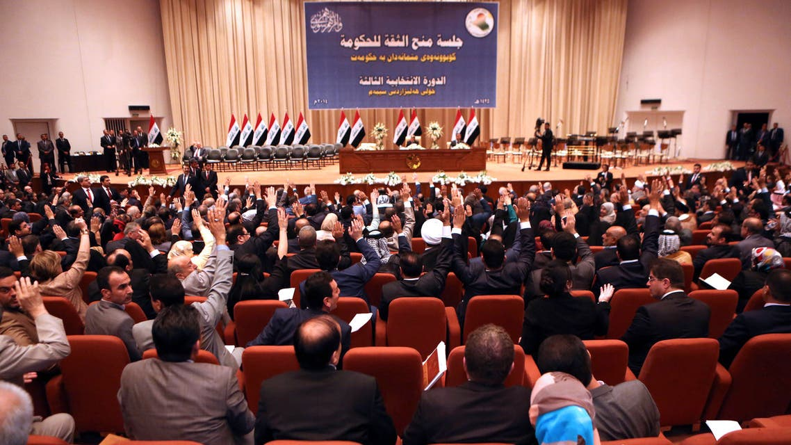 Iraqi lawmakers vote during a parliament session to approve the new government in Baghdad on September 8, 2014. Iraqi MPs approved a new cabinet but key security posts remained unfilled, as America's top diplomat prepared to visit the region to build a coalition against jihadists. AFP PHOTO / HADI MIZBAN / POOL