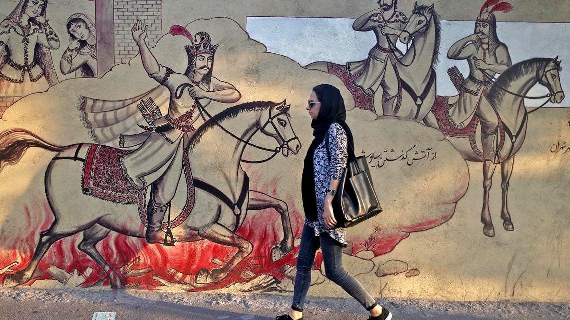 An Iranian woman walks past paintings of a Persian poetry in downtown Tehran, Iran, Monday, July 30, 2018. (AP)