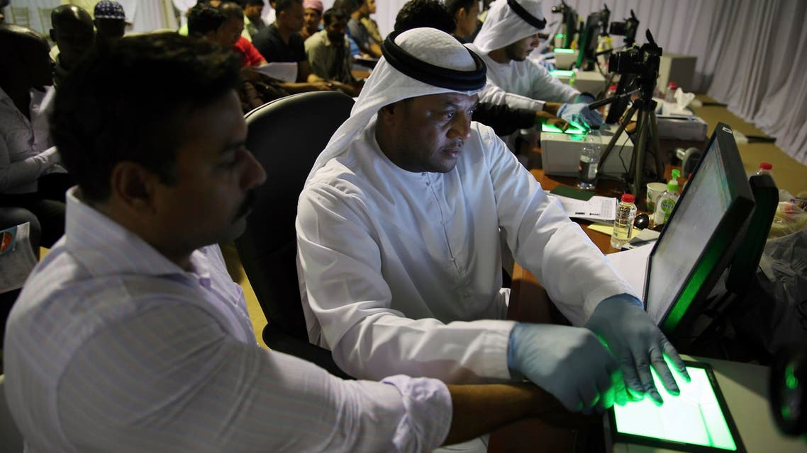 A government employee, left, takes the fingerprints of a foreign worker at a visa processing center in Al Aweer, about 30 km east of Dubai, on Aug. 1, 2018. (AP)