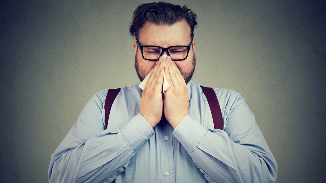 Sneezing chunky man posing on gray - Stock image