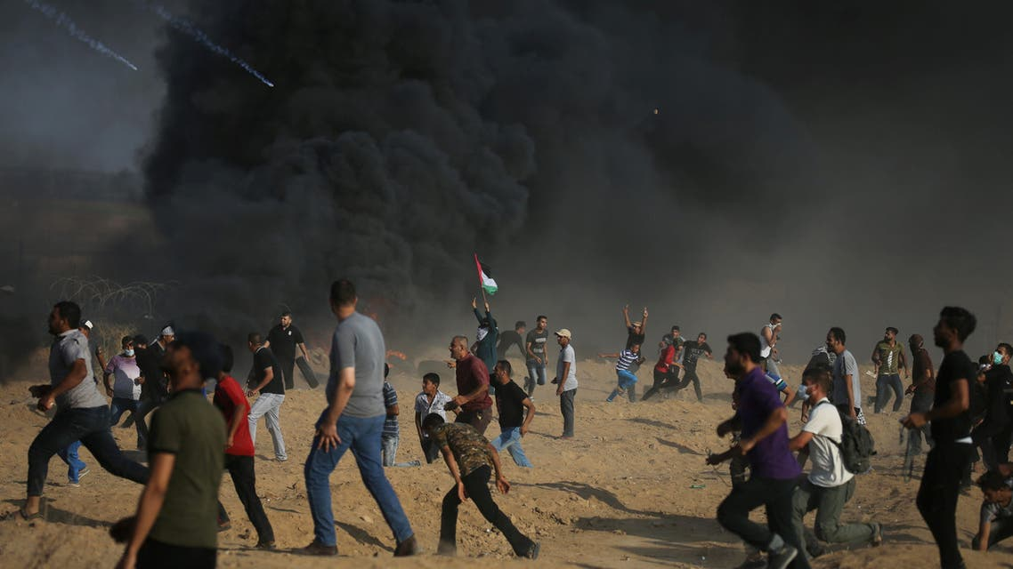 Tear gas canisters are fired by Israeli troops towards Palestinian demonstrators as they run during a protest demanding the right to return to their homeland at the Israel-Gaza border, in the southern Gaza Strip August 3, 2018. REUTERS/Ibraheem Abu Mustafa