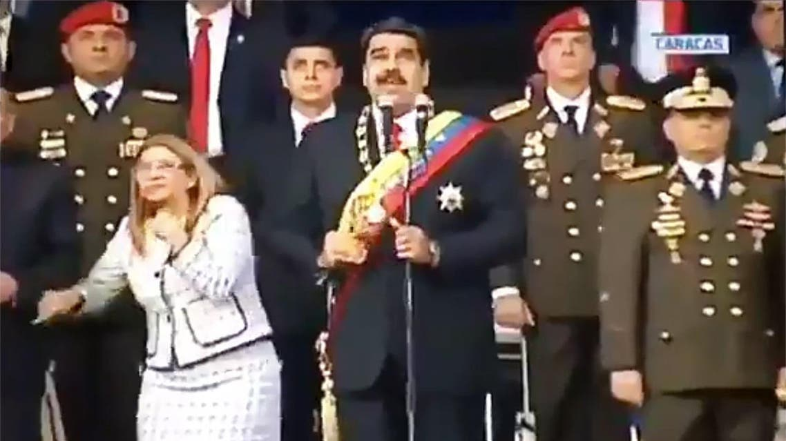 Screengrab taken from a handout video released by Venezuelan Television (VTV) showing Venezuelan President Nicolas Maduro (C), his wife Cilia Flores (L) and military authorities reacting to the attack. (AFP)