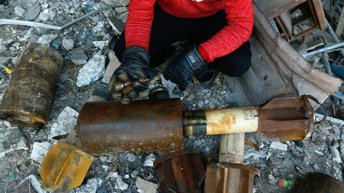 A Syrian man shows remnants of rockets reportedly fired by regime forces on the rebel-held besieged town of Douma in the eastern Ghouta region on the outskirts of the capital Damascus on January 22, 2018. At least 21 cases of suffocation, including children, were reported in Syria in a town in eastern Ghouta, a beleaguered rebel enclave east of Damascus, an NGO accusing the regime of carrying out a new chemical attack said.