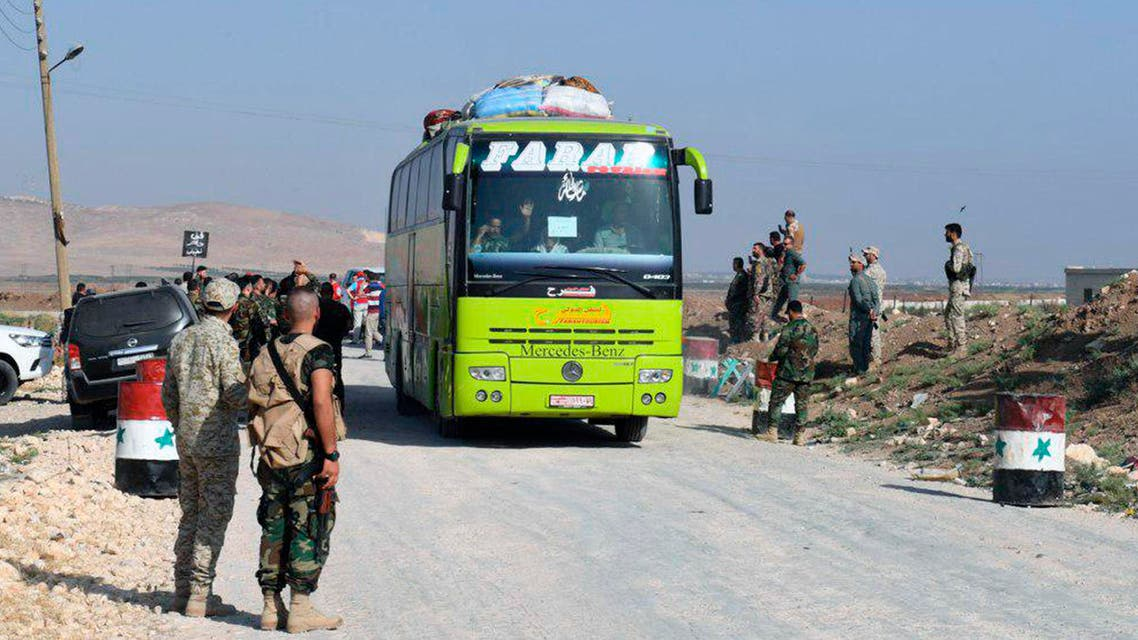 This photo released by the Syrian official news agency SANA, shows Syrian troops overseeing the evacuation of people in buses