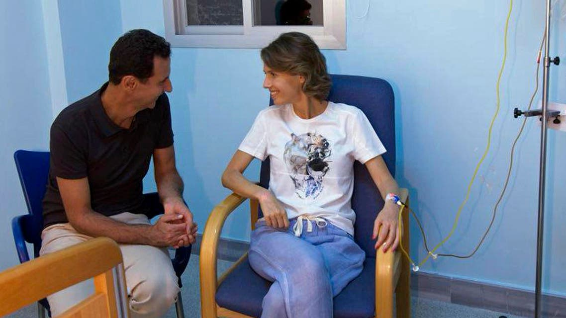 President Bashar Assad sitting next to his wife in a hospital room with an IV in her left arm. (AP)