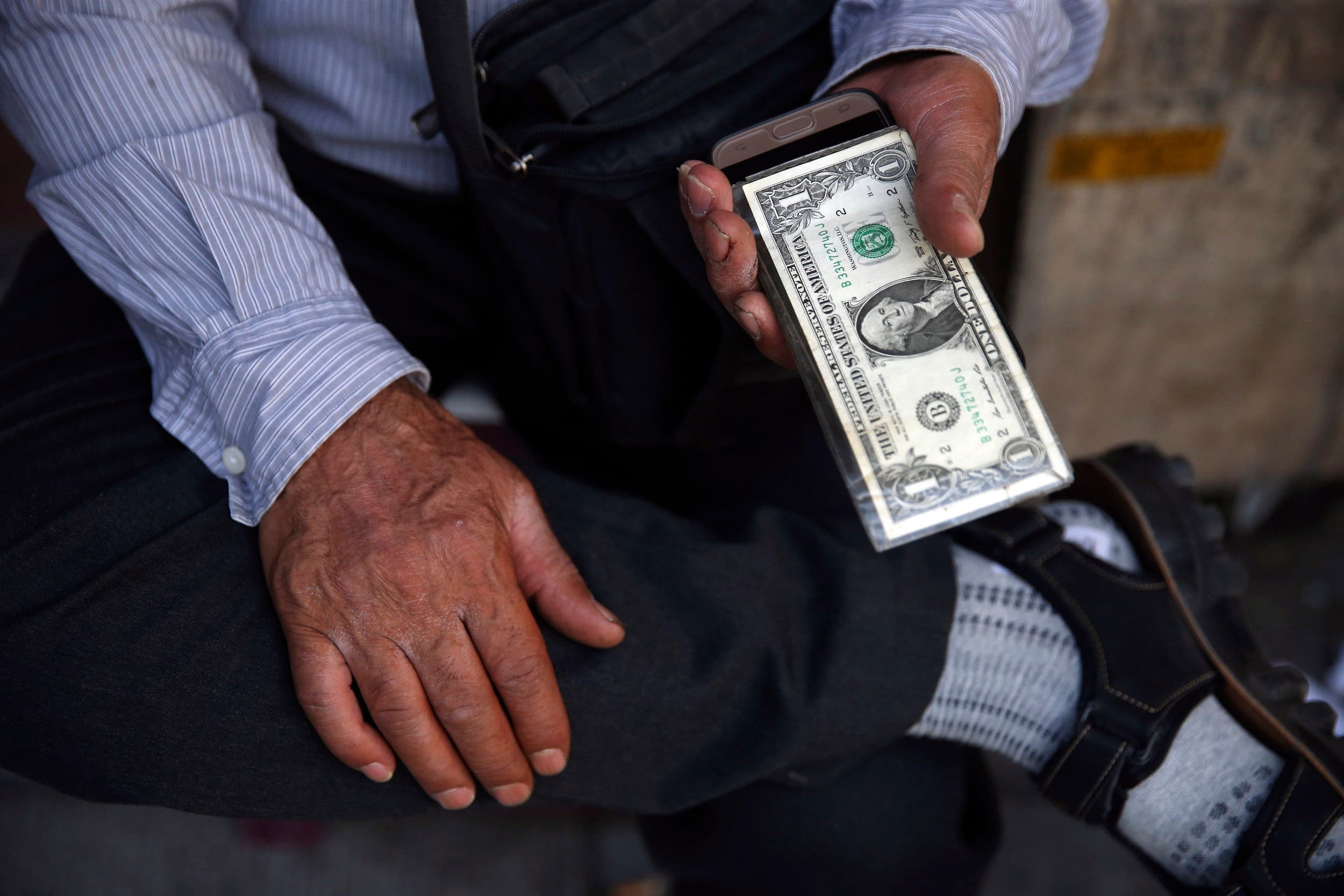 An Iranian street money exchanger holds US banknote in Tehran on July 30, 2018. (AP)