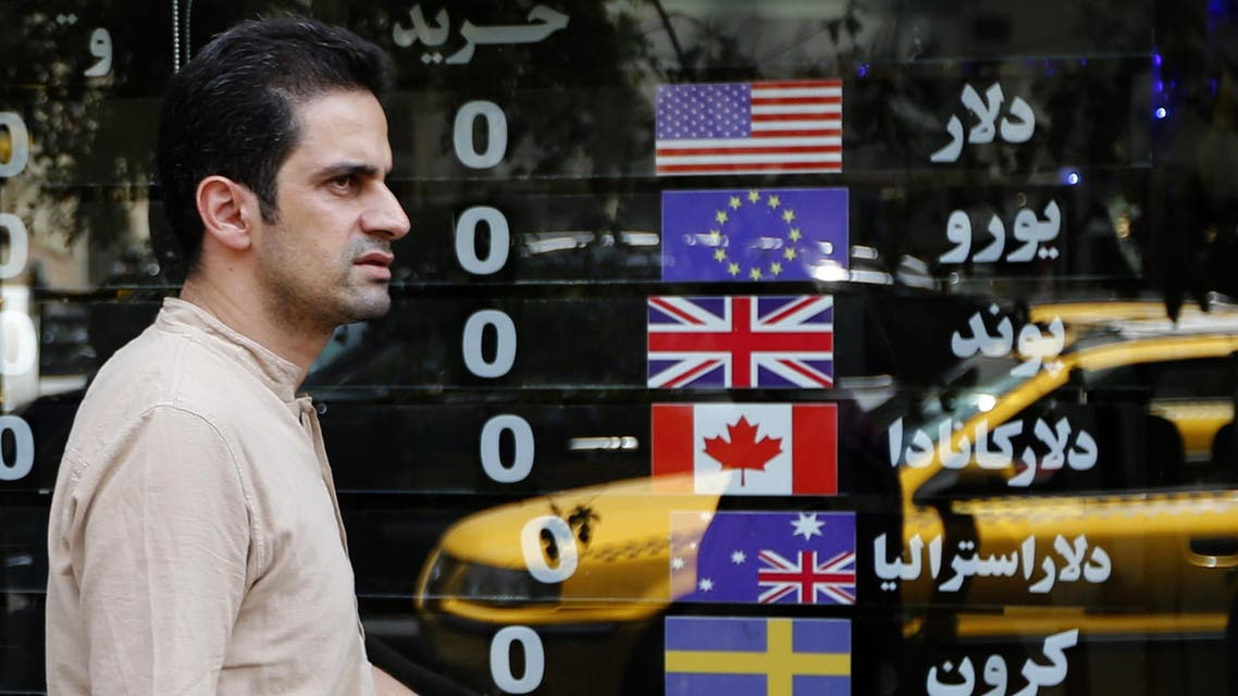An Iranian walks in front of a currency exchange shop in Tehran on August 8, 2018. (AFP)