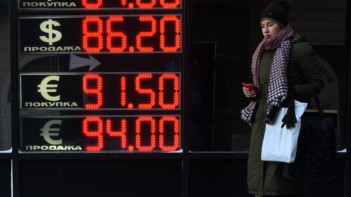 A woman walks past a board listing foreign currency rates against the Russian ruble in Moscow, on January 21, 2016. (File photo: AFP)