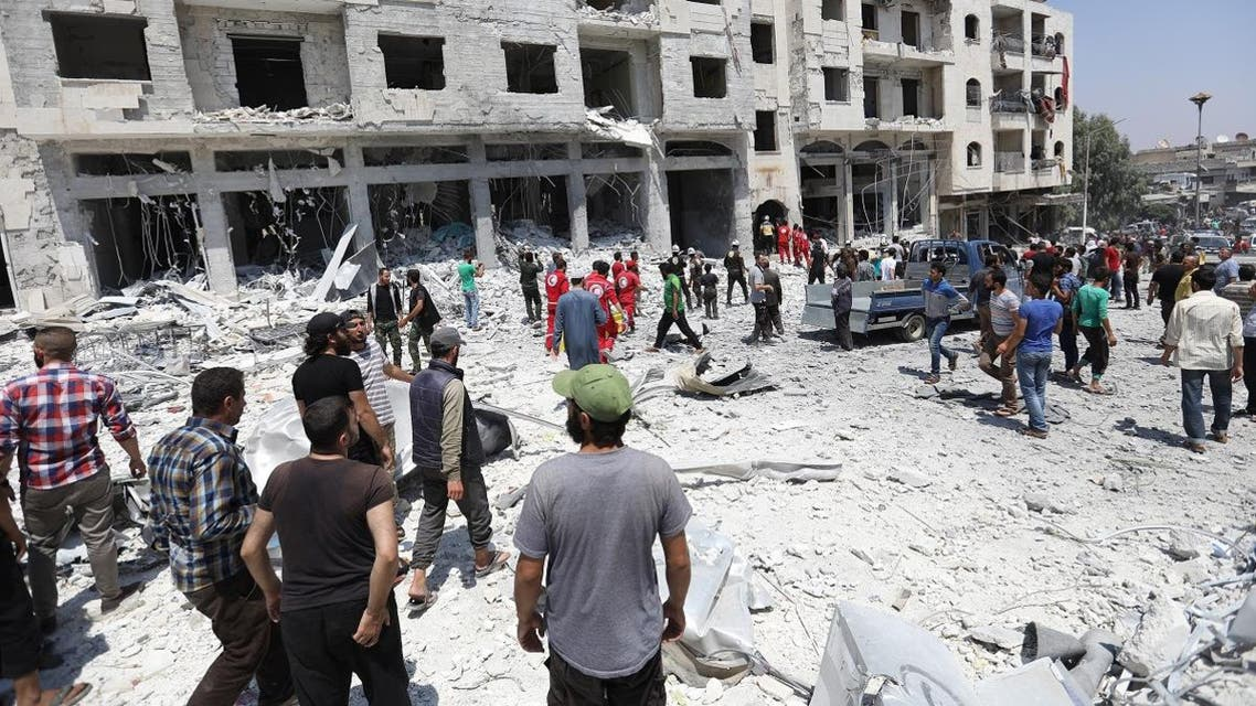 Syrians gather at a site of car bomb in the northwestern Syrian city of Idlib on August 2, 2018. (AFP)