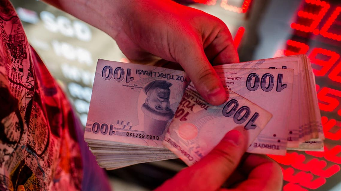 A money changer counts Turkish lira banknotes at a currency exchange office in Istanbul, on August 8, 2018. (AFP)
