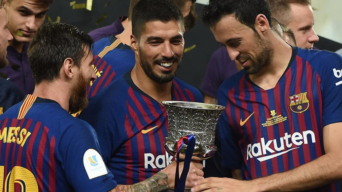 Barcelona's Argentinian forward Lionel Messi (2nd-L) presents the cup to Barcelona's Spanish midfielder Sergio Busquets (2nd-R) as they celebrate at the end of the Spanish Super Cup final against Sevilla FC in the Moroccan city of Tangiers. (AFP)