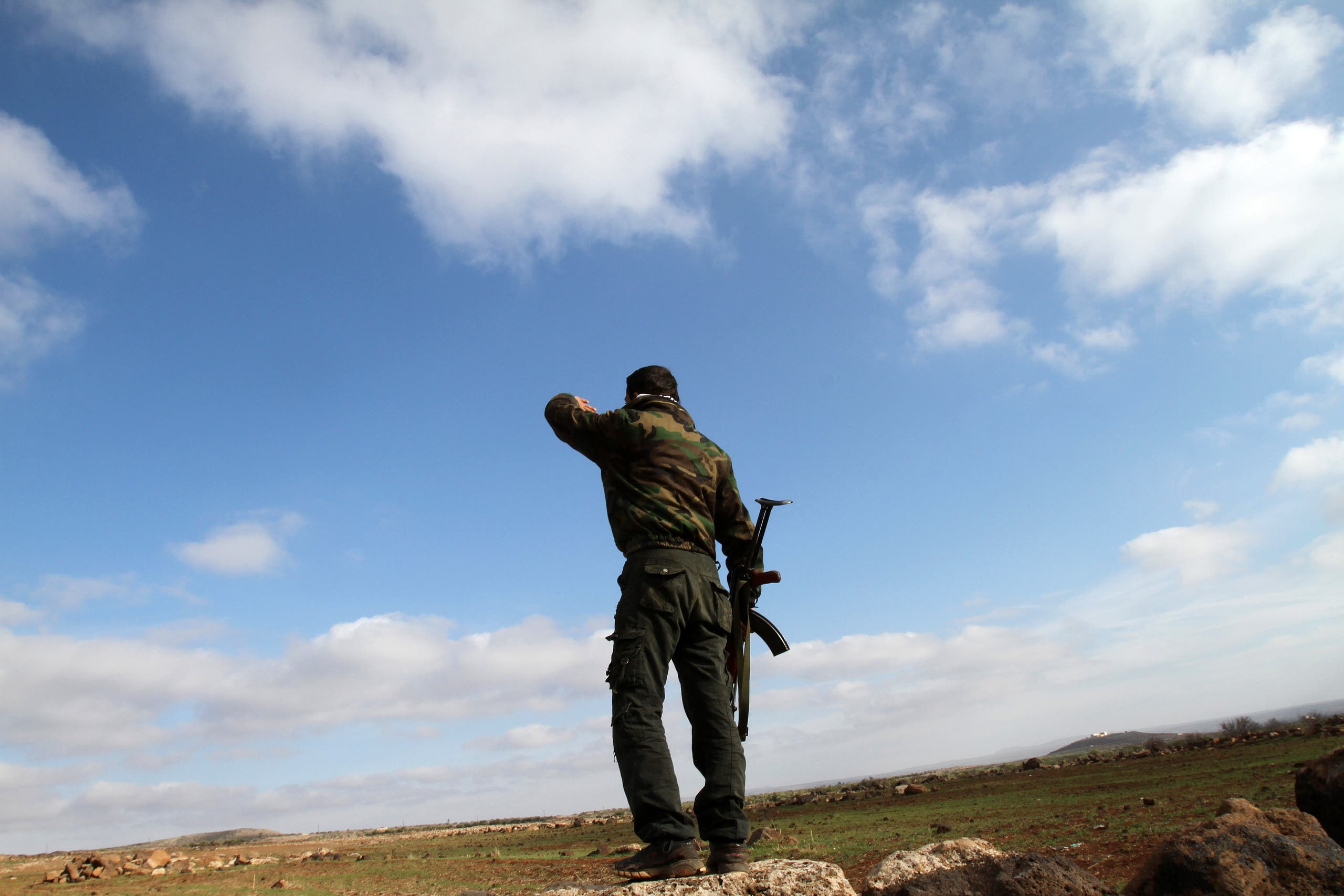 A Syrian soldier looks over at the town of Daraa from his position in the southern city of Sweida. (AFP)