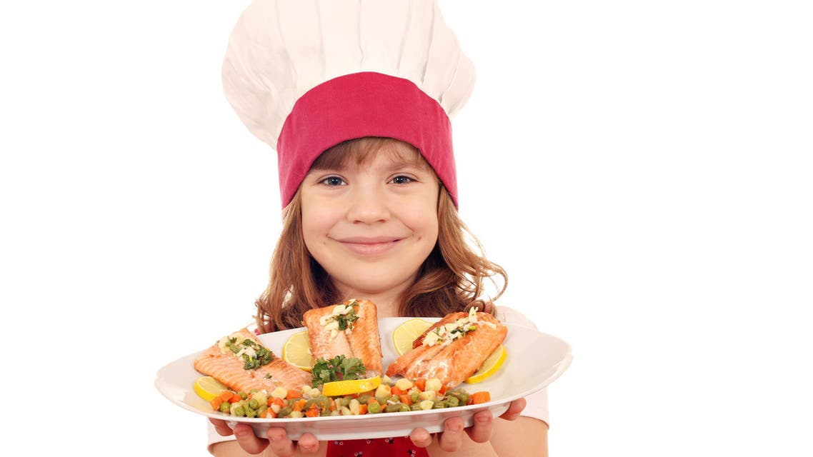 Happy little girl cook hold plate with salmon seafood - Stock image